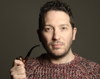 A person with short dark hair, wearing a knitted brown jumper, looks at the camera and holds a pipe