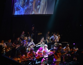 A group of children playing guitars on stage.