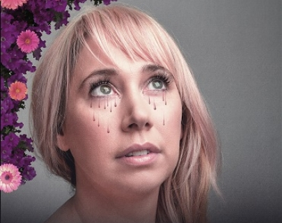 A blonde woman looking up with dark tears painted on her face and pink flowers on the left side of her head.