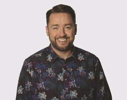 A bearded camera wearing a dark floral shirt smiles at the camera