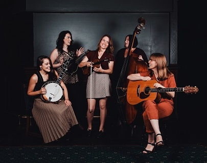 A group of women hold their instruments and laugh and talk together, in a dark room with a patterned carpet.