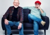 A photo of two men, sat on a sofa smiling, one of them is wearing a red hat and round sunglasses