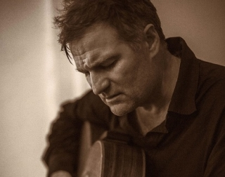 A close-up, sepia toned image of a man looking down and playing the guitar
