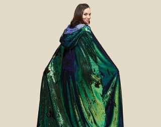 An image of a woman wearing a sparkly green cape