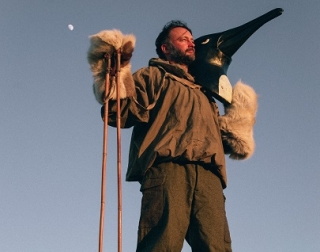 A man in old-fashioned hiking gear stands, looking into the distance, holding a large model penguin head on his shoulder.
