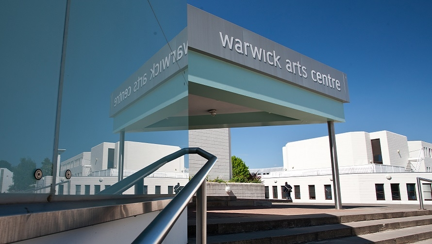 "An image showing Warwick Arts Centre from the outside. A set of steps is pictured, with a handrail going up, and a grey sign that reads ""Warwick Arts Centre""."