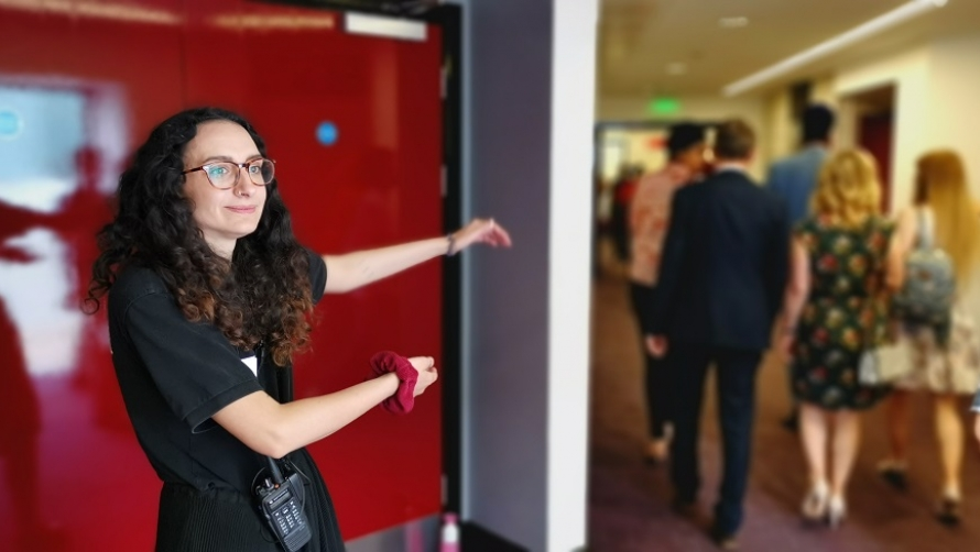 A Warwick Arts Centre steward stands in front of a red door and directs visitors to her left.