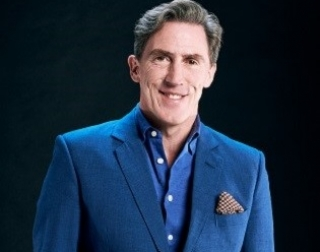 Rob Brydon in dark blue suit standing with hands in pockets set against a black background.
