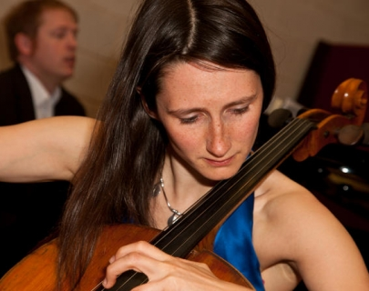 Female musician in a blue dress playing the cello