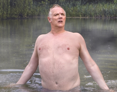 Greg Davies walking through a lake