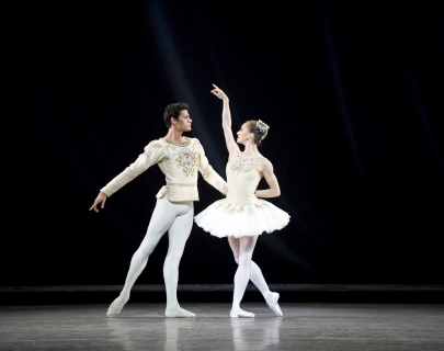 Two dancers in white costumes dancing on stage