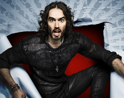 Comedian Russell Brand bursting out of a paper screen