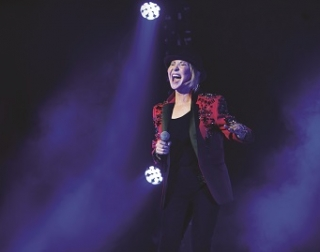 Lulu singing on stage wearing a red jacket