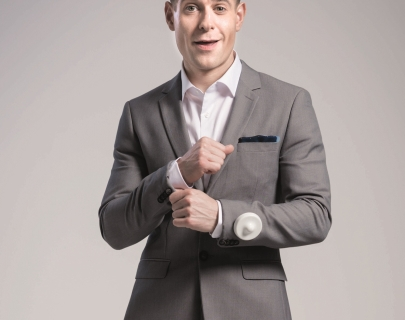 Comedian Lee Nelson in a grey suit on a white background