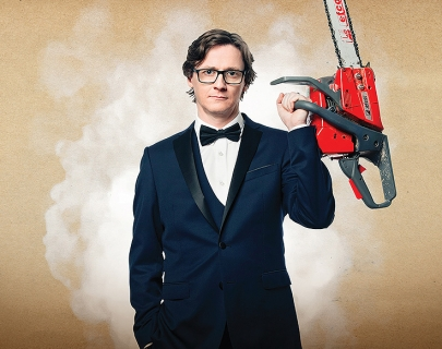 Comedian Ed Byrne in a tuxedo, holding a chainsaw!