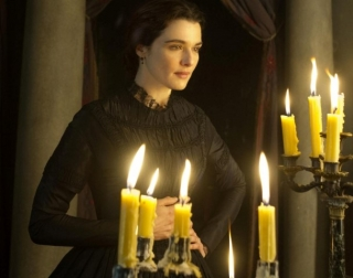 Actress Rachel Weisz in a black Victorian dress surrounded by candles