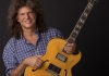 Musician Pat Metheny holding a guitar