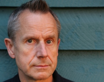 Comedian Jeremy Hardy on a blue background