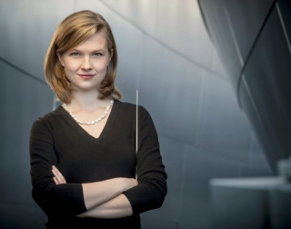 Conductor Mirga Gražinytė-Tyla holding a baton on a grey background