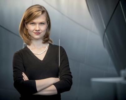Conductor Mirga Gražinytė-Tyla holding a baton on a grey background