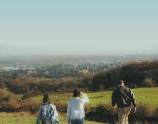 Rita, Sue and Bob Too - actors walking on a hill towards an industrial town