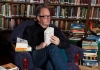 Robin Ince sat in a library full of books