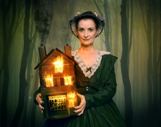 Woman in Victorian clothes holding a dolls' house