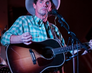 Comedian Rich Hall wearing a cowboy hat and holding a guitar