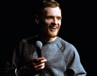 Comedian Andrew Lawrence holding a microphone