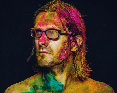 Steven Wilson wearing glasses and with bright coloured paint across his face