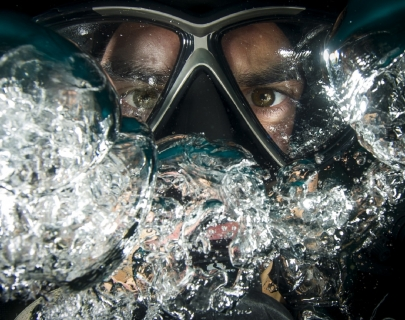 An underwater mask with water bubbles surrounding it