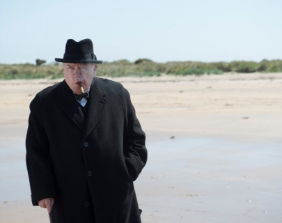 Actor Brian Cox walking on a beach smoking a cigar