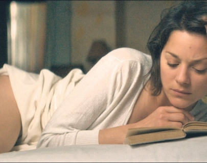 Actress Marion Cotillard lying on the bed reading a book