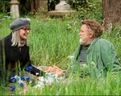 Actors Diane Keaton and Brendan Gleeson sitting on the grass