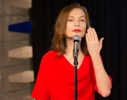 Actress Isabelle Huppert in a red dress singing in front of a microphone