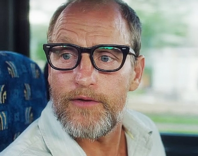 Actor Woody Harrelson wearing glasses on a bus
