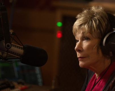 Actress Shirley MacLaine wearing earphones in a recording studio