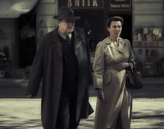 Actors Brendan Gleeson and Emma Thompson walking in the street in 40s clothes