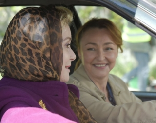 Actresses Catherine Deneuve and Catherine Frot sitting in a car