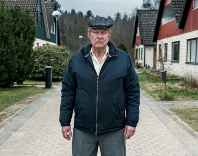 Actor Rolf Lassgård standing in the middle of a driveway