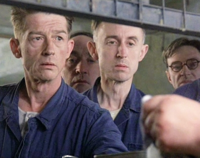 Actor John Hurt and other cast members in blue overalls
