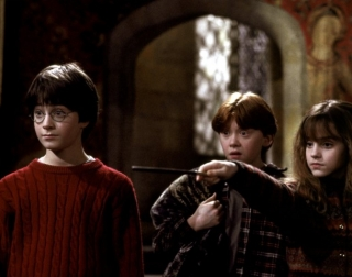Actors Daniel Radcliffe, Rupert Grint and Emma Watson in the dark Gryffindor common room