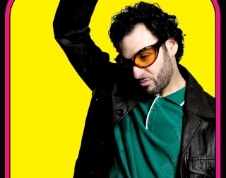 Comedian Patrick Monahan in yellow sunglasses and a leather jacket
