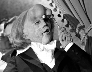 Actor John Hurt as The Elephant Man looking through a monocle