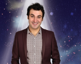 Patrick Monahan standing in front of a starry background