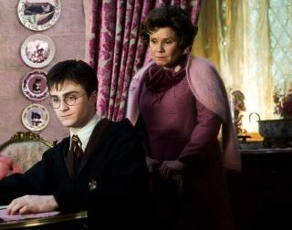 Actor Imelda Staunton watches actor Daniel Radcliffe writing lines
