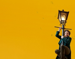 Actor Rory Kinnear hangs from an old fashioned lamppost in front of a bright yellow background