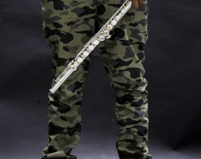 Man dressed in army combats holding a flute