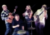 Urban Folk Quartet laughing and playing the drums, guitar, mandolin and fiddle