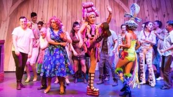 Cast of Priscilla in colourful costumes